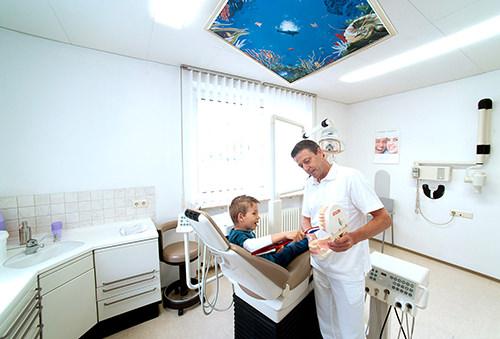 Dr. Hofmann erklärt Junge das Zähneputzen