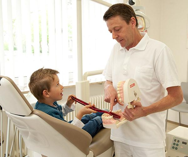 Dr. Hofmann erklärt kleinem Jungen das Zähneputzen