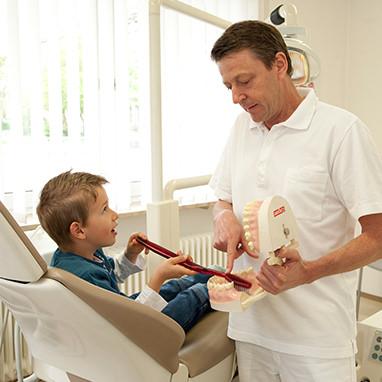 Zahnarzt erklärt kleinem Jungen das Zähneputzen