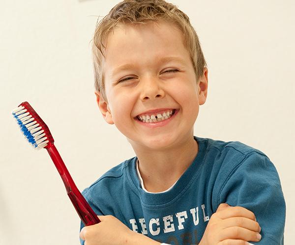 Prophylaxe bei Kindern und Jugendlichen - Junde mit Zahnbürste